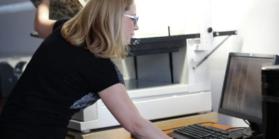 Side view on a woman librarian, at work, scanning large sheets of newspapers on a large eye book scanner, looking at the PC monitor to regulate the brightness or contrast of the scanned file