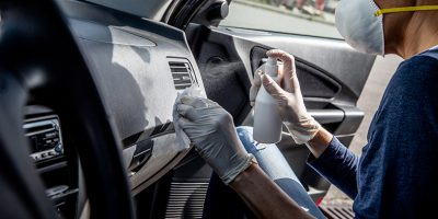 Adult Woman Disinfecting Car Dash Board with Antiseptic and Wet Wipe