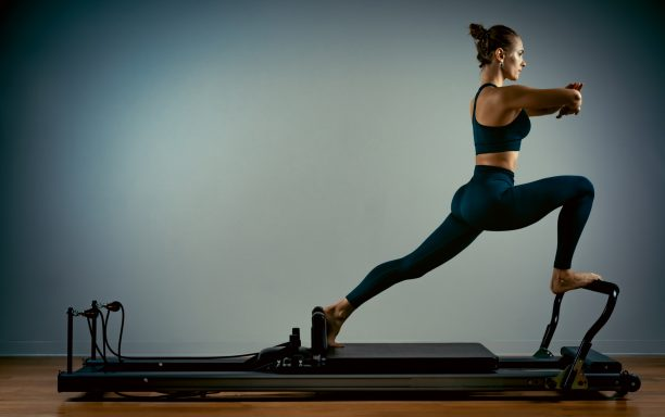 Young girl doing pilates exercises with a reformer bed. Beautiful slim fitness trainer on a reformer gray background, low key, art light, copy space advertising banner.